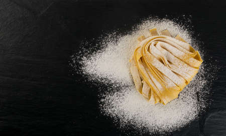 Raw yellow italian pasta pappardelle, fettuccine or tagliatelle close up. Egg homemade noodles cooking process, long rolled macaroni or uncooked floured spaghetti on black stone background top view