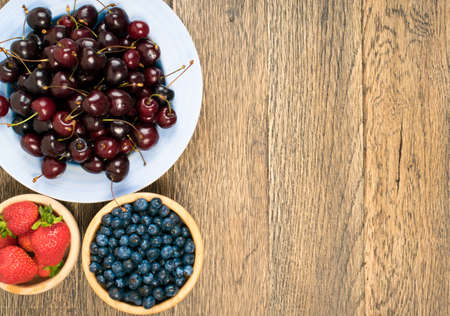 Fresh Summer Strawberries, Cherries and Blueberries on Old Vintage Wooden Background with Copyspace. Wood Table Desk Board Texture with Ripe Forest Berries Top View