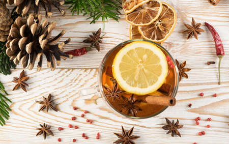 Winter drink with spices on festive new year background. Christmas tea with cinnamon, red pepper, anise and lemon on rustic woden background top view