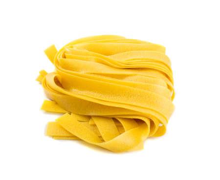 Rauwe gele Italiaanse pasta pappardelle, fettuccine of tagliatelle close-up. Ei zelfgemaakte droge lintnoedels, langgerolde macaroni of ongekookte spaghetti geïsoleerd Stockfoto