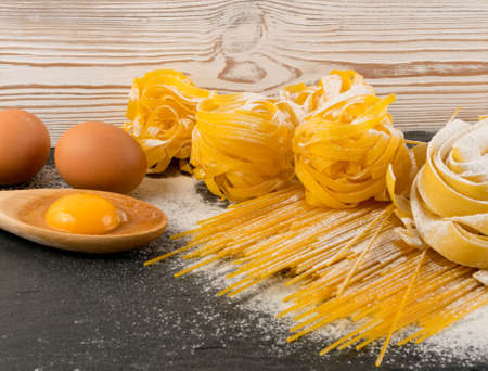 Raw yellow italian pasta pappardelle, fettuccine or tagliatelle close up with eggs. Egg homemade noodles cooking process, long rolled macaroni or uncooked spaghetti on black stone background Stockfoto