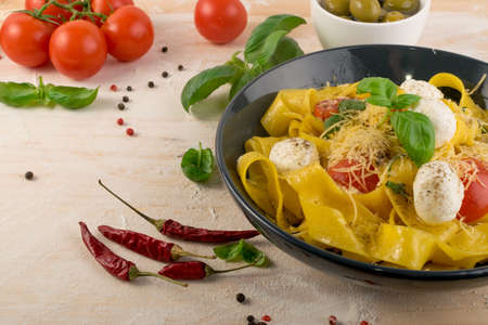 Macro photo of yellow cooked pasta pappardelle, fettuccine or tagliatelle in black bowl. Egg homemade ribbon noodles or macaroni with tomatoes, basil and mozzarella balls