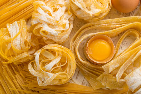 Raw yellow italian pasta pappardelle, fettuccine or tagliatelle close up with eggs. Egg homemade noodles cooking process, long rolled macaroni or uncooked spaghetti against flour background top view