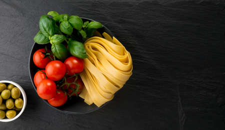 Raw yellow italian pasta pappardelle, fettuccine or tagliatelle top view. Egg homemade noodles, long rolled macaroni or uncooked spaghetti with olives, tomatoes and basil Stockfoto