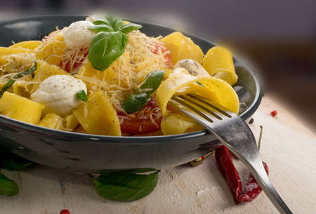 Macro photo of yellow cooked pasta pappardelle, fettuccine or tagliatelle on fork. Egg homemade ribbon noodles or macaroni with tomatoes, basil and mozzarella balls Stockfoto