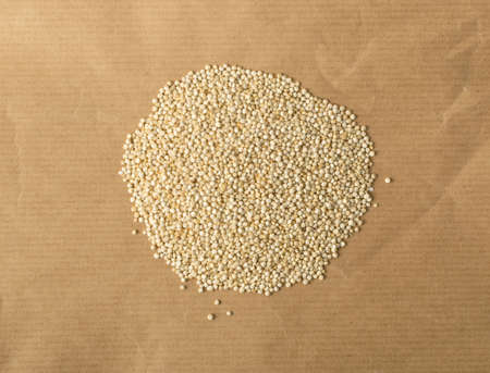 Heap of Gluten Free Quinoa Seeds Called Super Food on Paper Background. Dry Organic Chenopodium Quinoa, Kinwa or Kinuwa Grains Top View