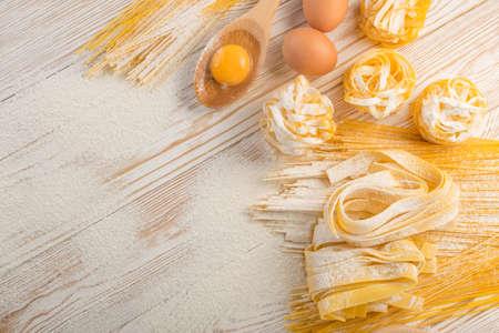 Rauwe gele Italiaanse pasta pappardelle, fettuccine of tagliatelle close-up met eieren. Ei zelfgemaakte noedels kookproces, langgewalste macaroni of ongekookte spaghetti tegen meel achtergrond bovenaanzicht