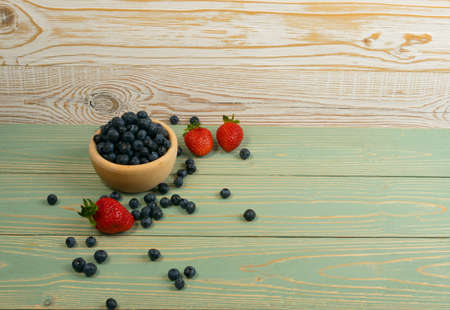 Fresh Summer Strawberries and Blueberries on Old Vintage Wooden Background with Copyspace. Turquoise Wood Table Desk Board Texture with Ripe Forest Berries