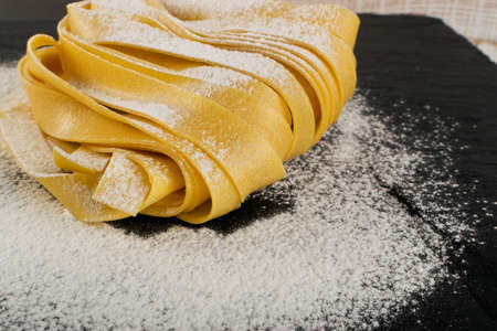 Raw yellow italian pasta pappardelle, fettuccine or tagliatelle close up. Egg homemade noodles cooking process, long rolled macaroni or uncooked floured spaghetti on black stone background