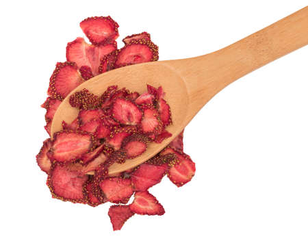 Group of home cooked dehydrated dry strawberries isolated on white background top view with clipping path. Dried homemade sliced organic strawberry berries in a wooden spoon close up