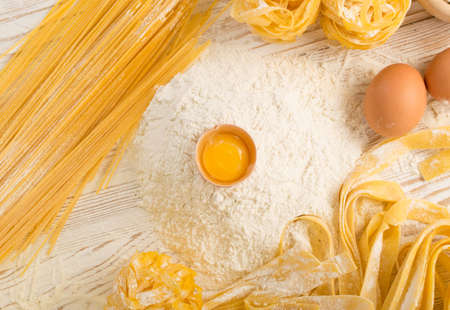 Raw yellow italian pasta pappardelle, fettuccine or tagliatelle close up with eggs. Egg homemade noodles cooking process, long rolled macaroni or uncooked spaghetti against flour background top view Stockfoto