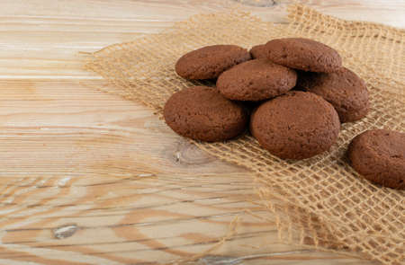 Heap of soft homemade chocolate butter cookie with chocolate filling on rustic table background. Brown round soft biscuits or fresh sweet cocoa buns closeup 스톡 콘텐츠
