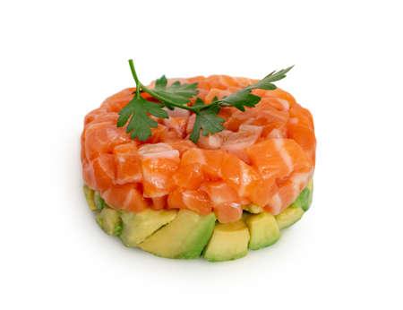 Raw salmon tartare, trout tartar or red fish cubes salad with fresh avocado closeup. Macro shot of delicious raw tuna steak tatar or sashimi on white restaurant plate