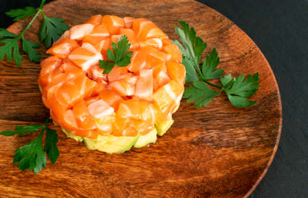 Raw salmon tartare, trout tartar or red fish cubes salad with fresh avocado closeup. Macro shot of delicious raw tuna steak tatar or sashimi on wooden rustic restaurant plate