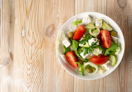Greek salad or horiatiki with large pieces of tomatoes, cucumbers, feta cheese and olives in white bowl top view, copyspace. Village salad with diced mozzarella, arugula, parsley, spices and oil Banque d'images