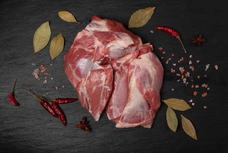 Fresh raw mutton shoulder meat with bone on black stone plate background. Large piece of sheep fillet or filet closeup top view Banque d'images