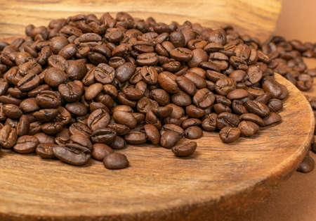 Dark brown whole coffee beans on wood background with copyspace. Roasted coffe grains on wooden texture for menu, banner template, wallpaper or recipe image design