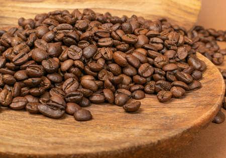 Dunkelbraune ganze Kaffeebohnen auf Holzhintergrund mit Exemplar. Geröstete Kaffeekörner auf Holzstruktur für Menü, Bannervorlage, Tapete oder Rezeptbilddesign