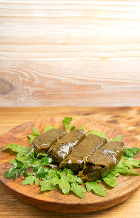 Macro Photo of Traditional Turkish Dolma, Sarma or Dolmades on Wooden Plate. Mediterranean Dish Dolmadakia or Tolma with Rice and Grapes Leaves Closeup with Copyspace Imagens