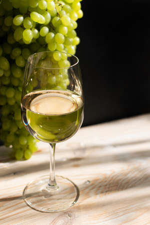 White wine glass on ripe bunch of grapes background in sunny day. Wineglass with golden grape sparkling drink on wooden rustic winery table 免版税图像