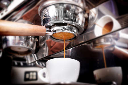 Macro shot of preparing espresso on professional coffee machine in coffeeshop or cafe closeup. Pouring strong coffee in small white cup