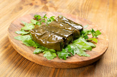 Macro Photo of Traditional Turkish Dolma, Sarma or Dolmades on Wooden Plate. Mediterranean Dish Dolmadakia or Tolma with Rice and Grapes Leaves Closeup