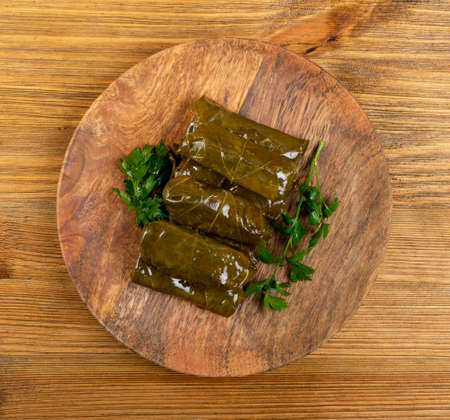 Traditional Turkish Dolma, Sarma or Dolmades on Wooden Plate Top View. Mediterranean Dish Dolmadakia or Tolma with Rice and Grapes Leaves Closeup