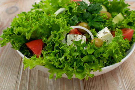 Greek salad or horiatiki with large pieces of tomatoes, cucumbers, onion, feta cheese and olives in white bowl closeup. Green village salad with diced mozzarella, lettuce, spices and olive oil