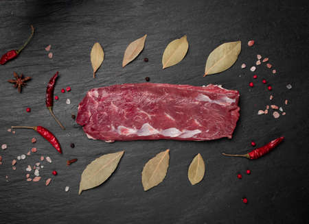 Raw lamb tenderloin fillet or mutton sirloin meat on black stone plate background. Fresh sheep fillet, loin filet with spices top view