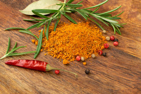 Pile of gyros kebap spices mix on wood plate. Blended pita kebab red spice powder with seasoned salts, grounded oregano, paprika, cumin, bay leaf, fresh rosemary, red pepper and chili pepper