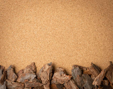 Line of Dry Pine Tree Bark Pieces on Brown Cork Board Background. Broken Woods Nature Chip on Cork Board Close Up