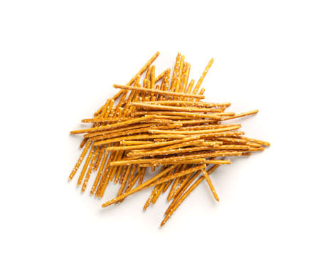 Pile of crispy salt sticks with white sesame isolated. Salty pretzel sticks, grissini or thin breadsticks top view