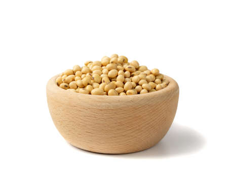Raw dehydrated soybeans isolated on white background. Dry soybeans in wooden bowl, pile of soya beans closeup