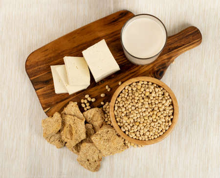 Soy foods collection with dry soy meat, soybeans, soy milk and tofu on rustic background top view. Soy products mix with soya milk, bean curd, soy protein or TSP