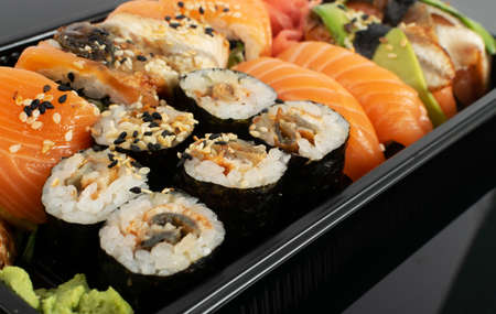 Macro photo of plastic container with sushi set ready for takeout delivery. Take away lunch box with susi rolls, nori maki and sushi nigiri