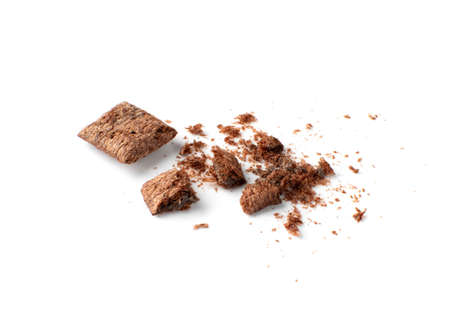 Crumbled chocolate pillows for breakfast isolated on white background. Broken choco cereal pads with cream, crispy corn flakes, healthy sweet snack