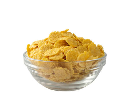 Yellow corn cereal for breakfast in round glass bowl isolated on white background. Pile of crispy corn flakes, cornflakes or cereals side view
