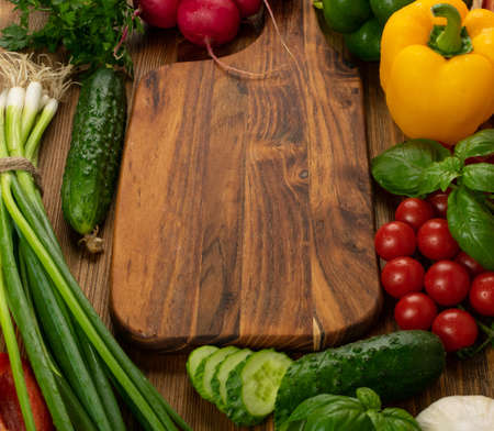 Cutting board vegetables mockup. Chopping board with fresh cucumbers, greens, peppers and cherry tomatoes ready for salad with copy space