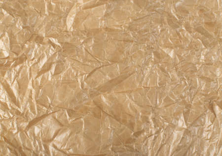 Sheet of Brown Thin Crumpled Craft Paper Parchment Background Top View. Wrinkled Tan Wrapping Paper Texture or Pattern Фото со стока