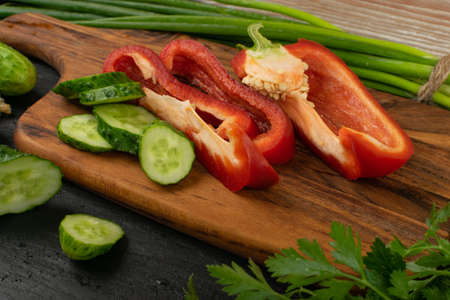 Sliced cucumber and bell pepper with green vegetables on rustic cutting board. Fresh cucumbers, red paprika, green onion or spring chive, basil and parsley ready for salad