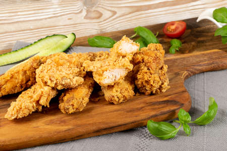 Breaded Deep Fried Fish Nuggets on Wooden Rustic Background. Hot Crispy White Fish Boneless Pieces in Breadcrumbs