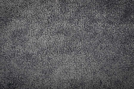 Gray carpet texture background top view. Dark gray nylon carpeting or mat pattern, nylon doormat wallpaper. Soft polyester carpet rug mockup with copy space