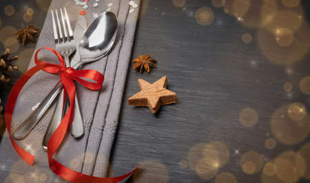 Christmas Dinner Table Setting with Cutlery, Gray Napkin and Winter Spices Top View. Festive Restaurant Decoration Background for Xmas Lunch, Dining invitation or Party with Copy Space