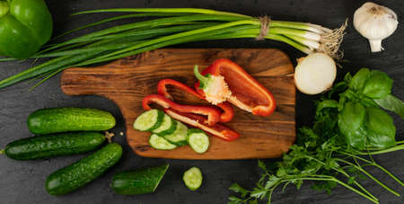 Sliced cucumber and bell pepper with green vegetables on rustic cutting board. Fresh cucumbers, red paprika, green onion or spring chive, basil and parsley ready for salad top view