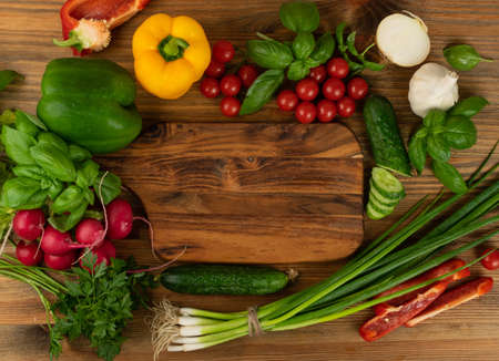 Rustic background mockup with cutting board and vegetables. Vintage chopping board with fresh greens, cucumbers, bell peppers, onion, cherry tomatoes ready for salad with copy space top view Фото со стока