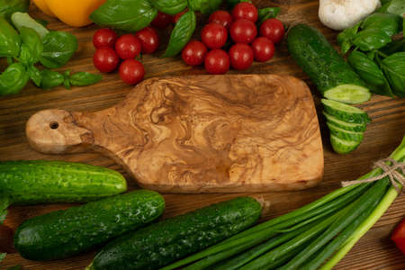Olive wood cutting board mockup. Chopping board with fresh green vegetables, greens and cherry tomatoes ready for salad with copy space top view Banque d'images