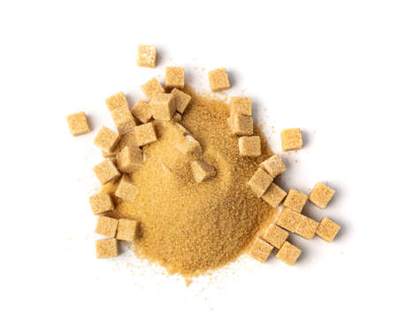 Brown sugar cubes isolated on white background. Pile of raw unrefined cane sugar sand heap top view