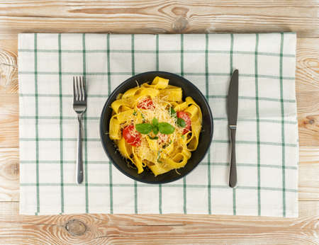 Homemade egg noodles on wooden rustic background. Yellow cooked pasta pappardelle top view. Fettuccine or tagliatelle on black plate and checkered tablecloth