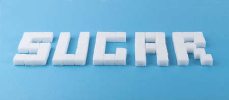 Sugar word made of white sugar cubes on blue background. Unrefined cane sugar cubes