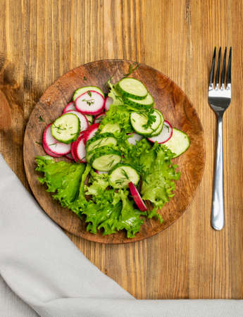 Spring homemade radish salad with fresh cucumber and greens on wooden plate top view. Simple green rustic salat with sliced radishes, cucumbers, escarole and lettuce